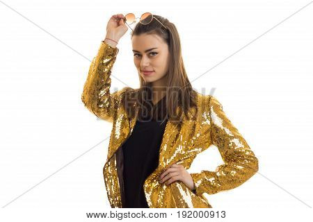 beautiful brunette in a gold jacket smiles at the camera isolated on white background
