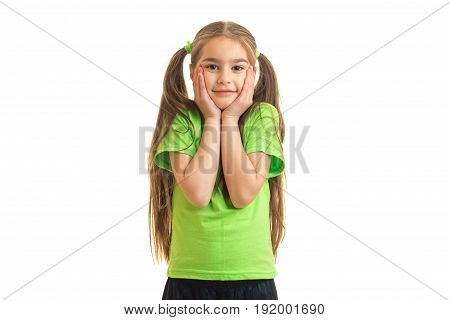cute little girl in the green shirt looks and smiles at the camera isolated on white background