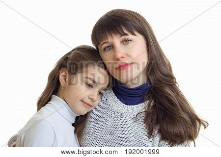 Portrait of mother and daughter cuddling isolated on white background