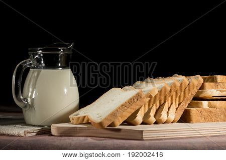 vase with milk and slices of bread on the table on black background