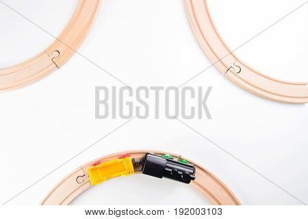 Toy train and wooden rails on white background. Top view