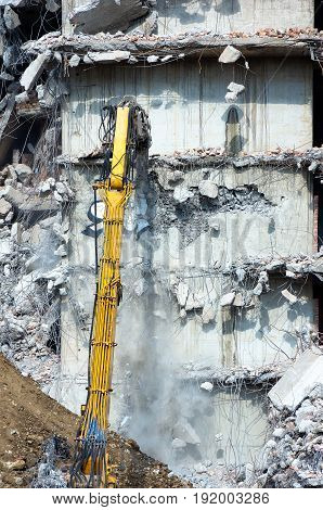 Remove a dangerous building in an urban area with a digger