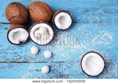 Coconuts With Candies On Blue Wooden Table