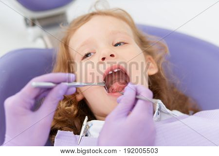 Close-up shot of little girl sitting at unrecognizable dentist while she making oral examination in hospital. Dentist and child in cabinet. Little girl sitting in the dentists office