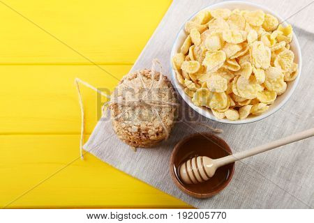 Cornflakes With Bowl Of Honey On Yellow Wooden Table