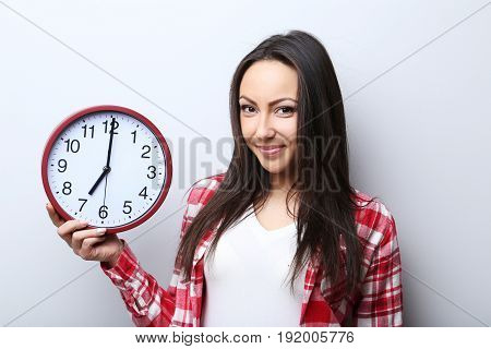 Young woman holding a clock on grey background