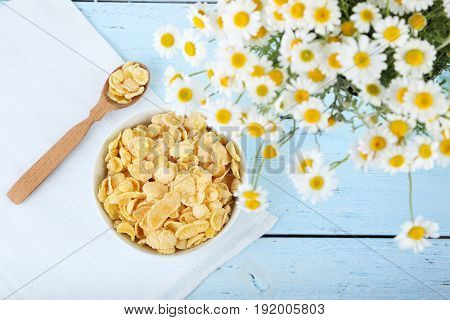 Cornflakes in bowl with chamomile on blue wooden table