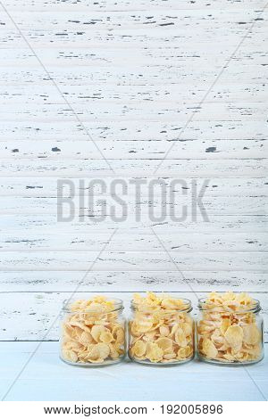 Cornflakes In Glass Jar On Wooden Table