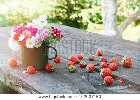 Bouquet of garden flowers in green enameled mug and strawberries on old wooden table outdoors.