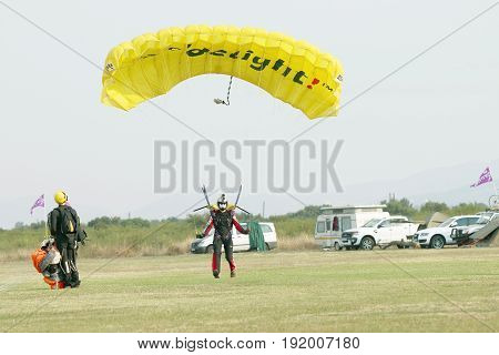 Masked Skydiver Coming In For Landing On Grass With Open Bright Yellow Parachute.