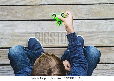 Child playing with fidget spinner outdoors. Top view