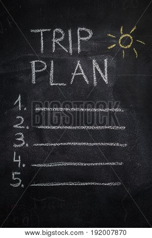 Trip plan list written with white chalk and yellow sun drawing on blackboard. To do list, trip, vacation concept