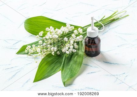 Lilies of the valley (convallaria majalis) and essential oil in vial on white textured background. Aroma of lily-of-the-valley is actively used in cosmetics production of perfumes hygiene products