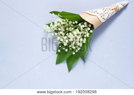 Delicate bouquet of lily of the valley (convallaria majalis) on pale blue background. Spring flowers: symbol of humility innocence return of happiness