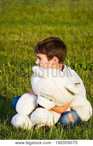Lonely boy hugging teddy bear and sitting on the grass