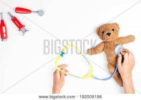 Kid hands with toy stethoscope, teddy bear and toy medicine tools on a white background. Top view. Copy space for text