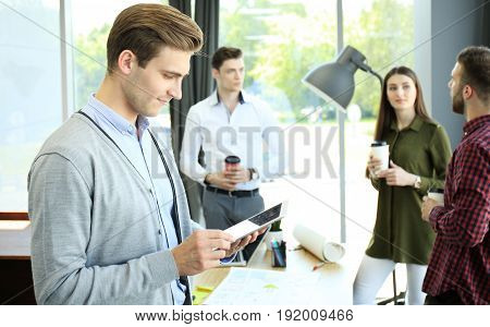 Smiling young man using digital tablet in the office