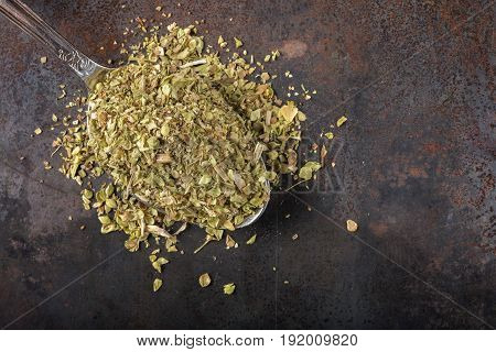 Spoon filled with dried oregano on rusty background with copy space