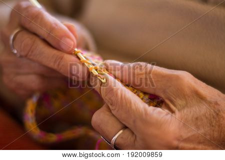 Close-up of the hands of an old lady who is crocheting with multicolored wool