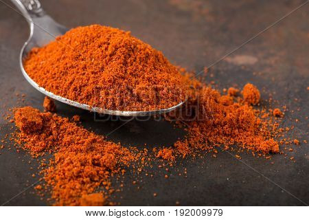 Spoon filled with paprika powder on rusty background