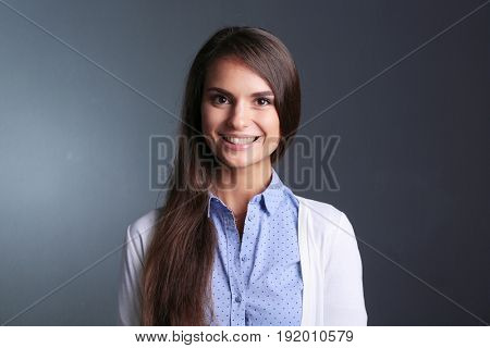 Portrait of a businesswoman , against dark background. Woman smi