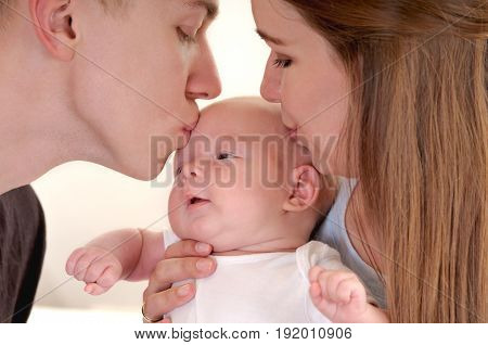 Closeup portrait of beautiful young family with newborn. Young parents both kissing their sweet baby. Happy parenthood