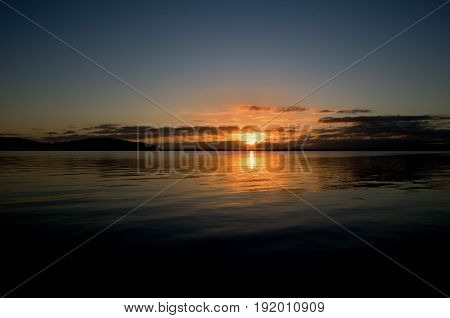 Gold and grey sunrise seascape with water reflections in the tranquil waters of Lake Macquarie at dawn. New South Wales Australia.