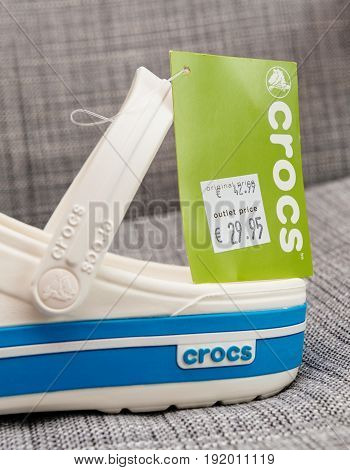 PARIS FRANCE - OCT 27 2016: Detail of new pair of Crocs foam clogs on gray background with regular and outlet reduced price. Crocs is a worldwide company selling comfortable shoes