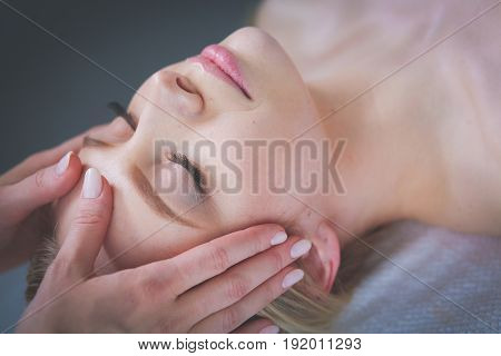 Young woman lying on a massage table,relaxing with eyes closed.