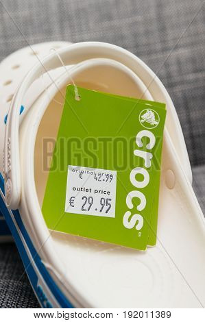 PARIS FRANCE - OCT 27 2016: Pair of new Crocs foam clogs on with regular price tag and outlet price tag reduction. Crocs is a worldwide company selling comfortable shoes