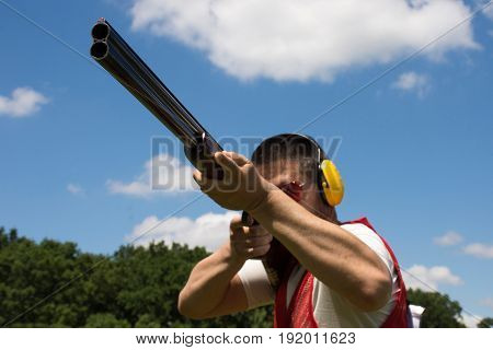 Man shooting skeet with a shotgun.   shotgun, skeet, trap