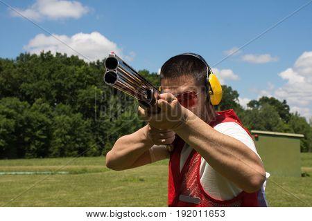 Man shooting skeet with a shotgun.  shotgun, skeet, trap