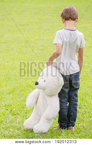 Sad lonely boy with teddy bear standing in the meadow. Back view. Sadness, fear, frustration, loneliness concept