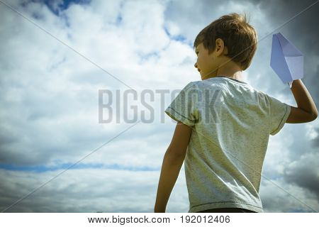 Little kid throwing paper plane. Low angle view