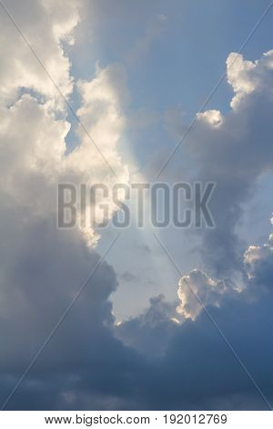 Clouds on blue sky pierced by ray of sunlight vertical