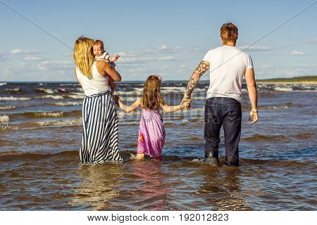 Beautiful, happy family in summer at sunset by the sea. Beautiful landscape. Family walks on the sea. Parents and two children. A view of the people from behind.
