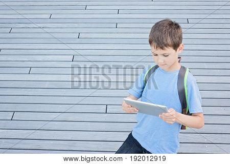 Kid using tablet computer outside. School, education, learning, technology leisure concept