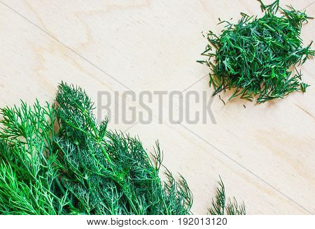 Bunch of dill on a wooden board. Next to a handful of chopped dill. Fennel close-up.