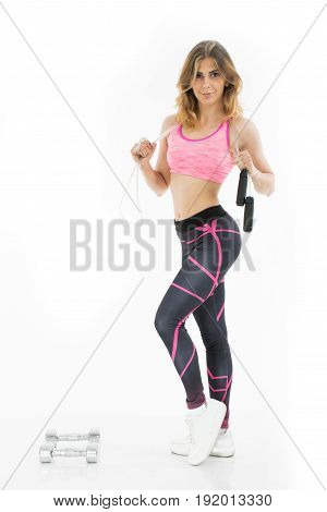 Young atletic woman with jumping rope. Attractive girl.