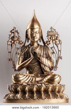 Bodhisattva Avalokiteshvara - a figure from bronze sitting on a white background in a pose of a lotus a hands in Dkharmachakra-mudra.
