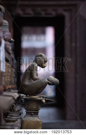 Gift from monkey of durian for Buddha. The old sculpture made of bronze. Gold temple Lalitpur Kathmandu Nepal.