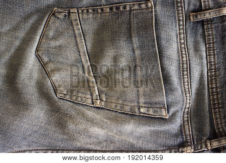 Back pocket jeans close-up. Rubbed old jeans close-up.
