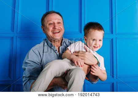 Laughing grandfather with his grandson as they play together indoors in the living room with the cute young boy hugging him from behind