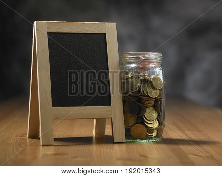 saving jar with coins and message board by the side