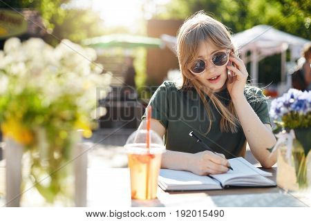 Portrait of a young business woman or student writing her plans in notepad talking on a smartphone wearing glasses during a luch break in park on a sunny summer day. Copy space.