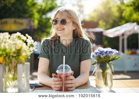 Young beautiful female student blogger taking a break from classes drinking grapefruit lemonade smiling looking off camera wearing glasses in park during a food festival on a sunny summer day.