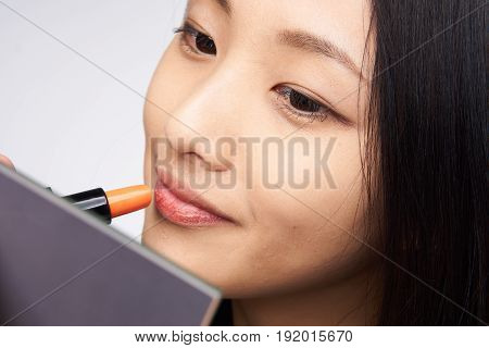 Woman is painting lipstick, woman with lipstick, woman is looking in mirror on light background portrait.