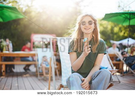 Girl eating ice cream laughing. Portrait of young woman sitting in a park on a sunny day eating icecream looking on camera wearing glasses enjoying summer.