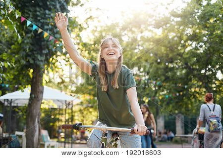 Girl riding bike in park. Portrait of a young female riding a bycicle outdoors and waving her friends or boyfriend smiling. Healthy lifestyle concept.