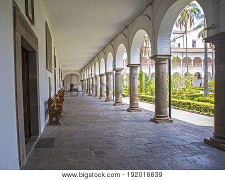 Corridors, columns and benches of the interior patios of the San Francisco church, in Quito, Ecuador.